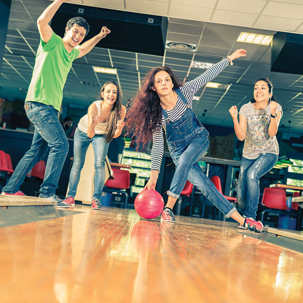 Youth friends bowling down lane